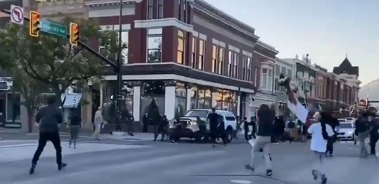 A zoomed-in video shows one protestor pulling a firearm and shooting at the SUV.