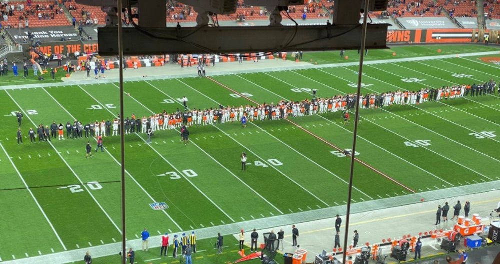 The Bengals and Browns stand together for the singing of the national anthem